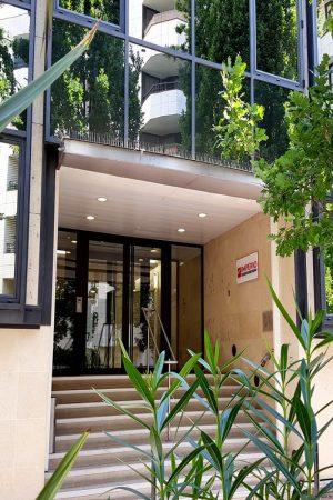 Porte d'entrée de l'entreprise IMPERIO. Plantes, verdure, fenêtres