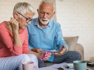 Senior couple having a hard time at home, calculating incoming bills and debt.